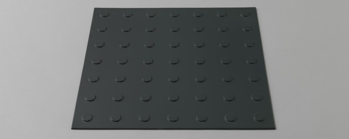Produktbild på varningsplatta av gummi, mörkgrå.