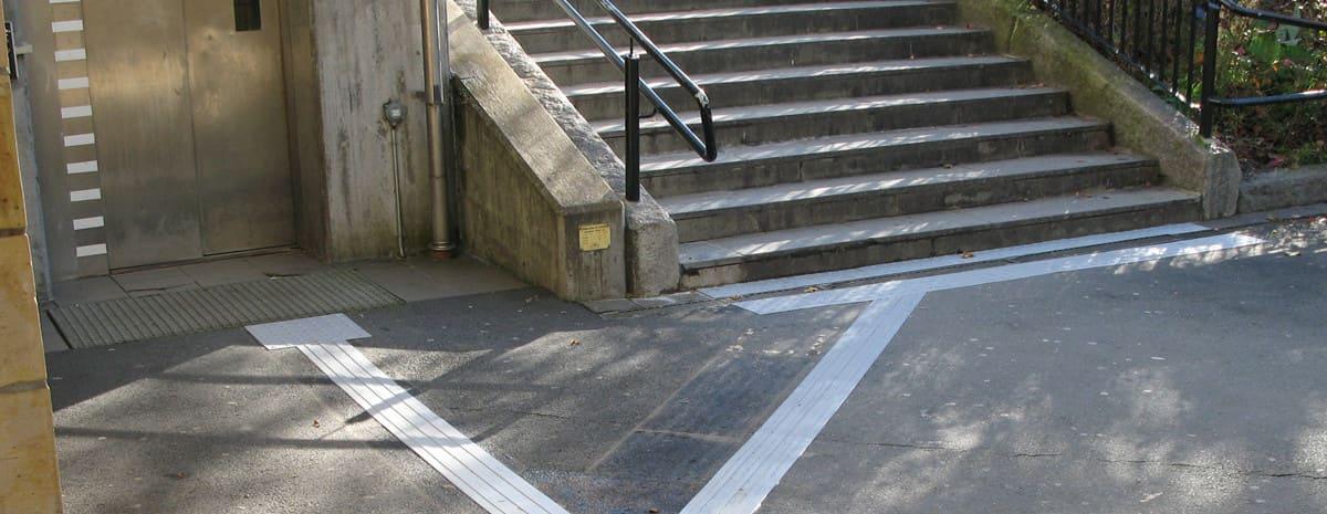 Taktila ledstråk av gummi installerade i utomhusmiljö på Herrljunga station. Ljusgrått ledstråk som leder fram till uppmarksamhetsmarkeringar vid hiss till vänster och trappa till höger.