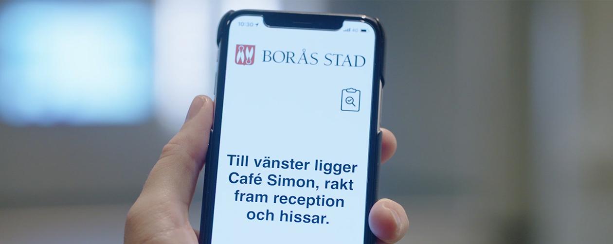 Tactile Flooring App - A smarter wayfinding. Bilden visar en hand med en mobiltelefon. I fönstret på mobilen visas en informationstext: Till vänster ligger Café Simon, rakt fram reception och hissar.