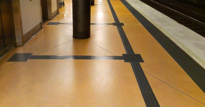 Skyddstråk närmast perrongkanten och ledståk som går parallellt. Här syns två valytor med stråk som leder till hissar.