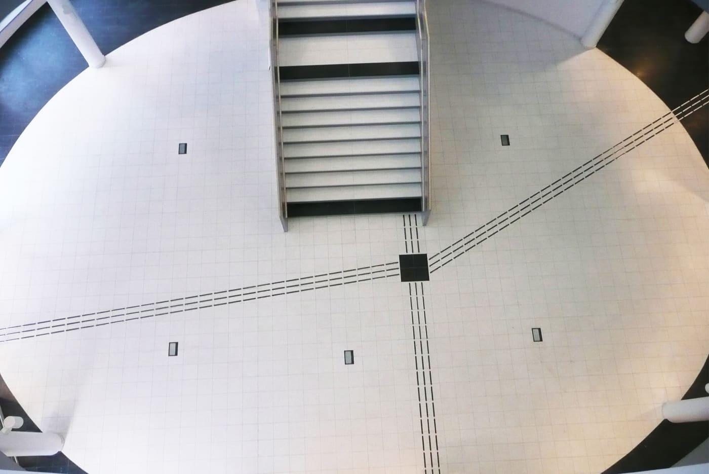 Bild från CNG i Finspång, fotad högt ovanifrån, visar ledstråk av rostfria element med Polypropylen. På det vita kakelgolvet är element med svarta inlägg och på det mörka golvet övergår elementen till vita inlägg.