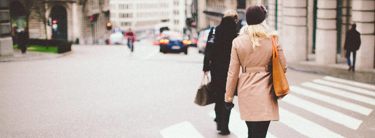 Bild visar ett övergångsställe i stadsmiljö med ryggtavlorna av två passerande personer.