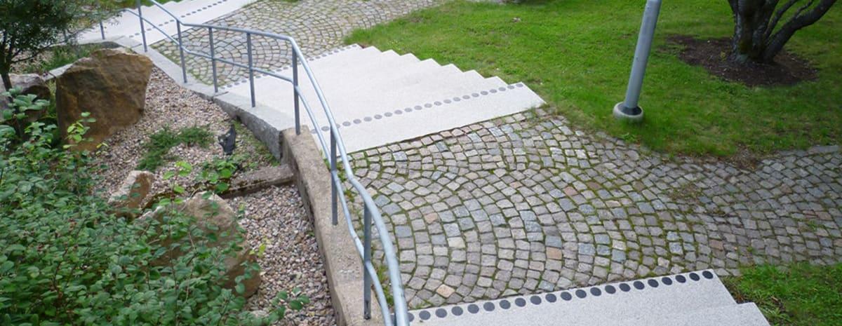 Kontrastmarkerade trappsteg i parkmiljö utomhus. Trapporna ligger i tre etage med avsatser med gatstensbeläggning.