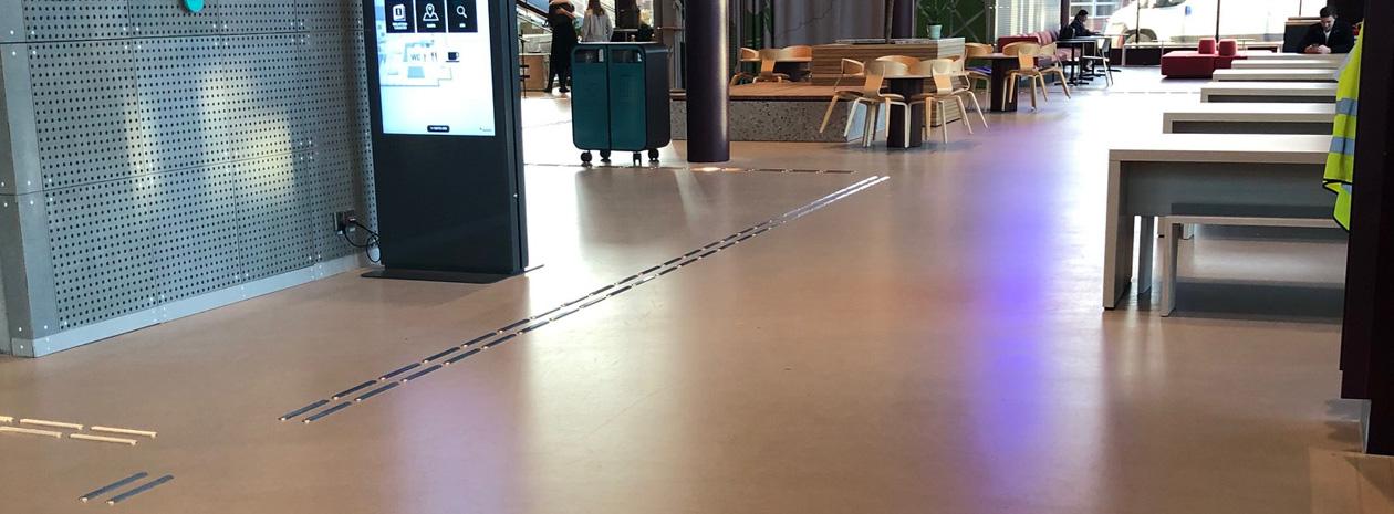 Taktila ledstråk Line av rostfritt stål visar vägen i studenthuset Campus Valla i Linköping.