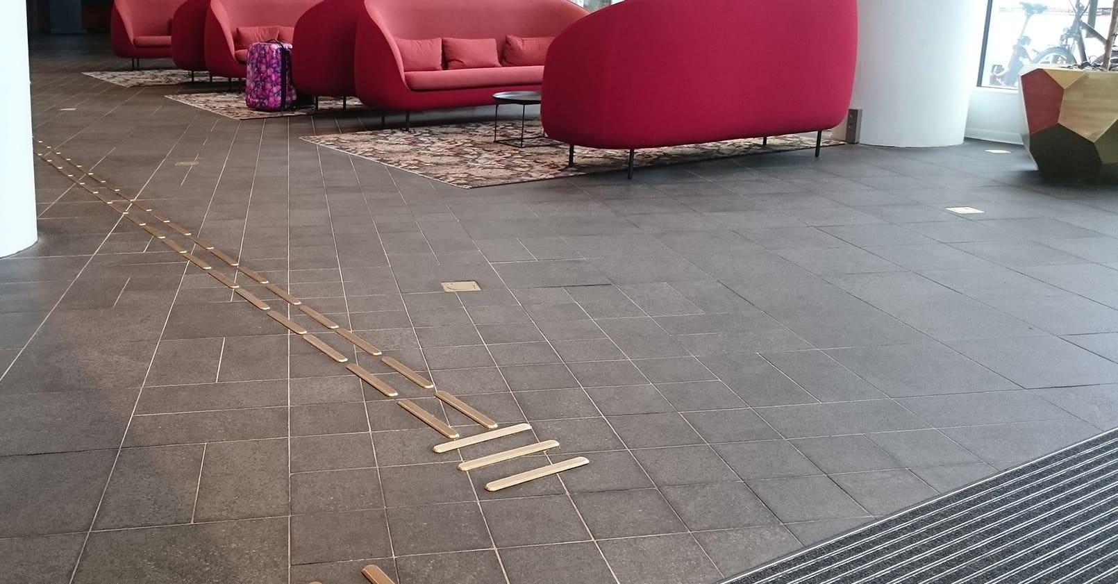 Bild från hotellentrén på Malmö Live där taktila ledstråk i mässing leder in i bygganden.