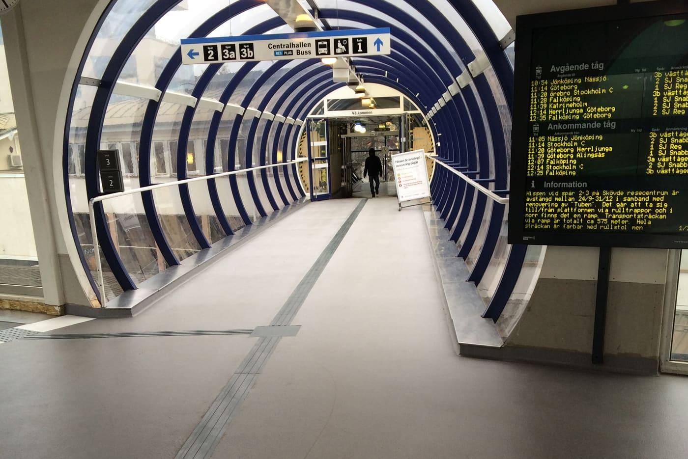 Bild från Skövde resecentrum. Mörkgrått gummiledstråk som visar vägen mellan perrongerna i gångtunneln ovanför spåren. Stråket avslutas med en varningsplatta vid rulltrappan.