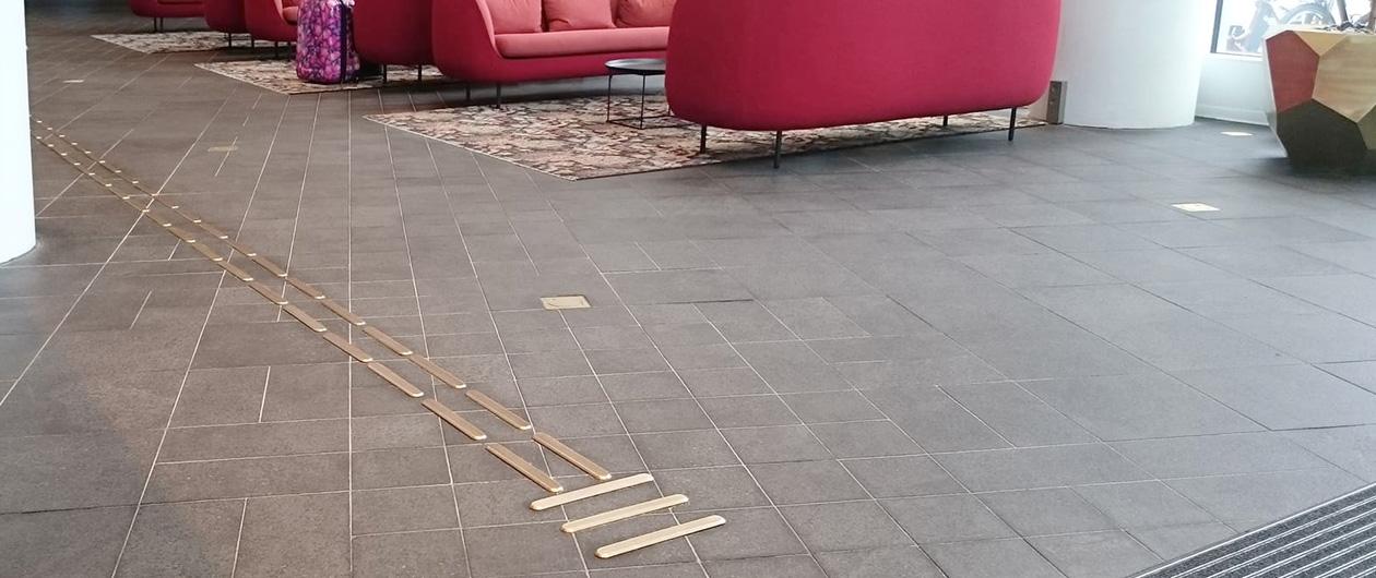 Taktila ledstråk i mässing i hotellentrén på Malmö Live.