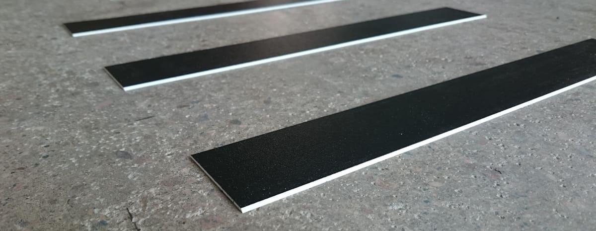 Närbild på svarta ledstråk av materialet akryl. Ledstråkets kant är fasat och har en ljus ton.