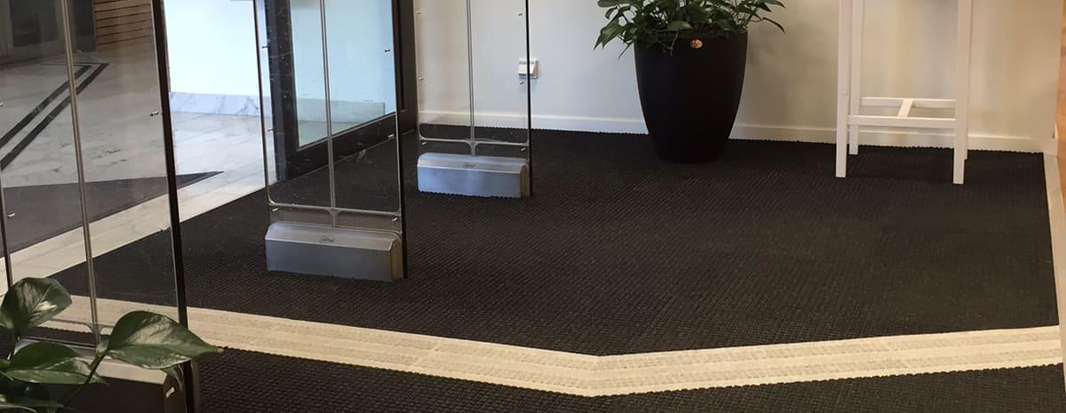 Visar entrémattan Combi Tile i svart med ett infällt vitt ledståk. Stråken har en tydlig taktil yta för att underlätta för personer med käpp.