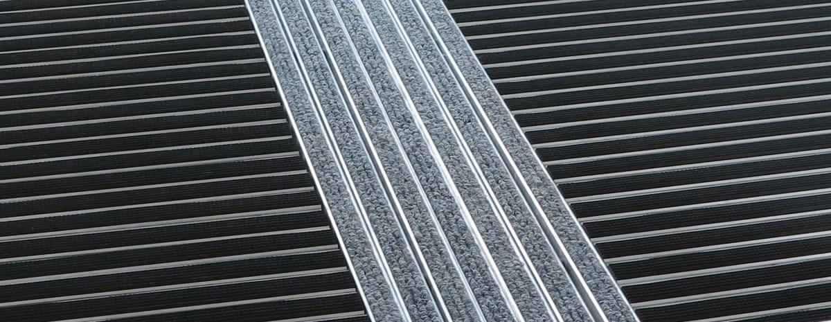 Närbild på taktilt ledstråk ATF 122 med inlägg i ljusgrå nålfilt. Entrémattan vid sidan av stråket är en aluminiumprofilmatta med svart gummi-inlägg.