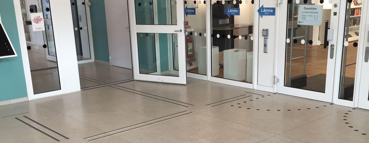 Bilden visar en entréhall med aluminiumledstråk för taktil och visuell vägledning i byggnaden. Framför glasdörrarna så finns uppmärksamhetsmarkeringar för dörrsvepen, likaså finns det på dörrarnas rutor.