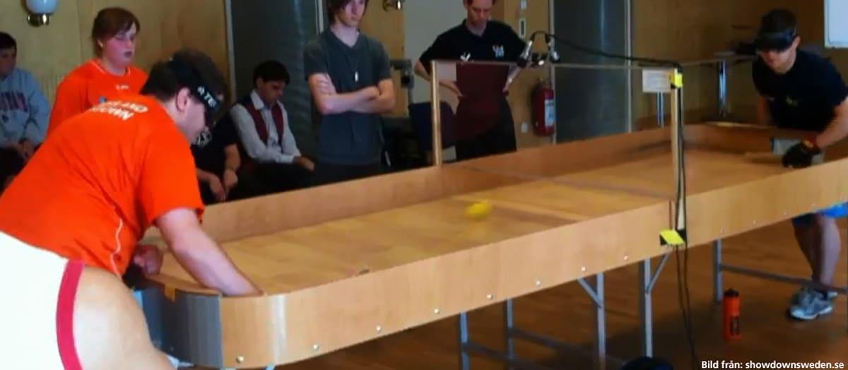 Två killar med ögonbindel spelar Showdown-match, fem personer tittar intresserat på. Bild hämtad från showdown.se