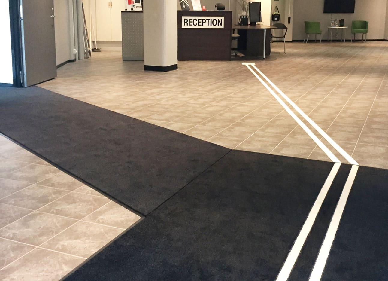 Bild från entrén på Träffpunkt Simonsland i Borås. Visar en svart Maximus-matta med vitt visuellt ledstråk tryckt på mattan. Där mattan tar slut börjar ett vitt ledstråk av aluminium som leder fram till receptionsdisken.