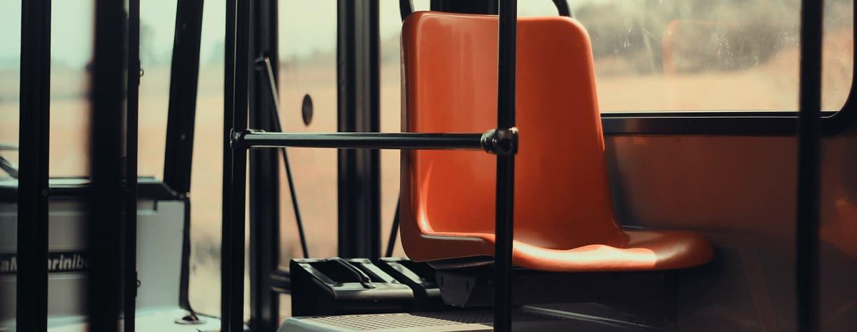 """Bilden symboliserar """"att resa till jobbet"""" och visar ett orange passagerarsäte i en buss."""