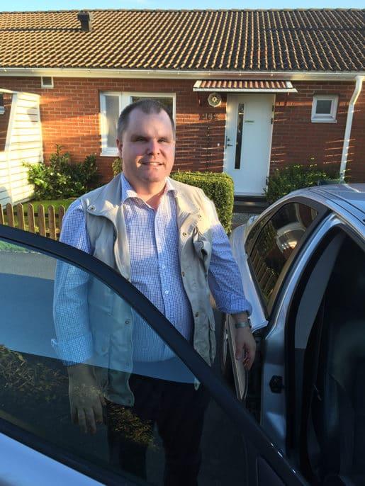 Fredrik på väg att stiga in i bilen. Det är en tidig vacker septembermorgon med hemmets entré i bakgrunden.