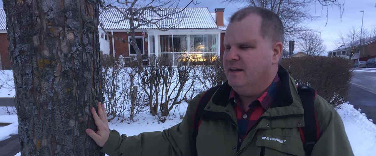 Fredrik känner på en trädstam, omgärdas av ett snöigt vinterlandskap i skymning.