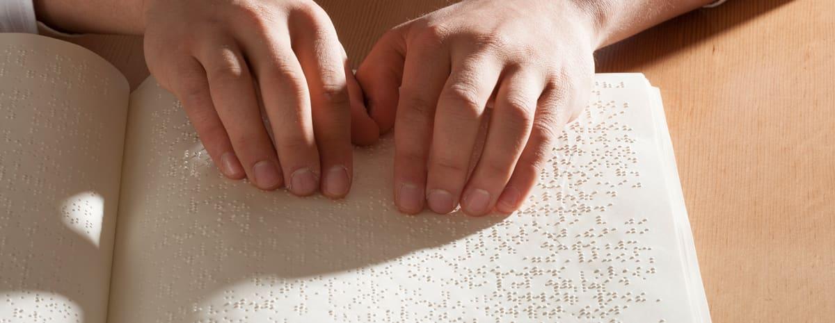 Närbild av händer som läser en bok med punktskrift.