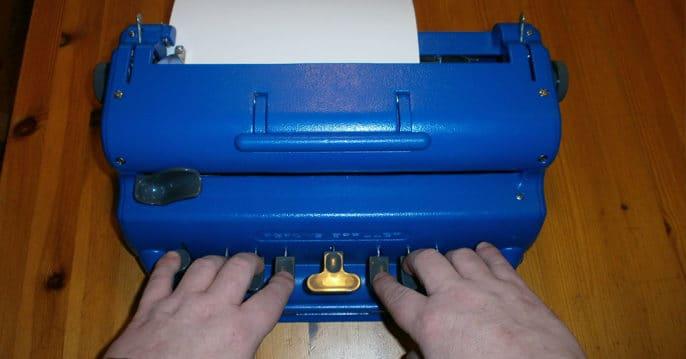 Fredrik skriver på sin blå blindskriftsskrivmaskin av märket Perkins.