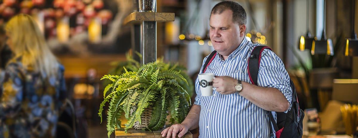 Fredrik dricker kaffe, ståendes vid ett bord på kafé. Bredvid på bänken står en vacker grön ormbunke.
