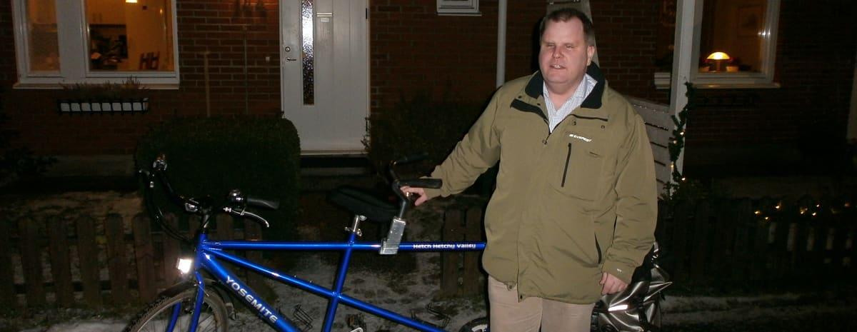 Fredrik står med sin blå tandemcykel framför sitt radhus/parhus.