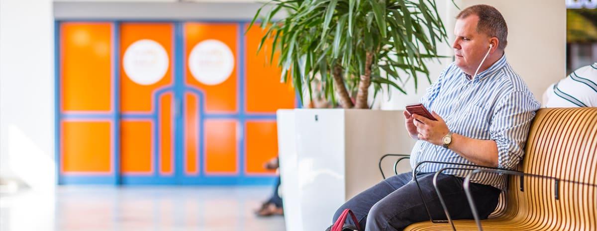 Bild från ett resecentrum där Fredrik sitter på en soffa, i handen håller han sin mobil. I bakgrunden skymtar en kruka med ett träd och där bakom en dörr i vackert orange och blått.