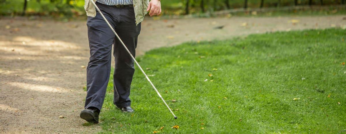 Klippt bild som visar underkroppen på Fredrik som promenerar i en park med vit käpp. Han använder gräskanten intill grusgången som ledstråk/hållpunkt.