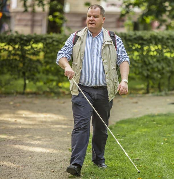 Helbild på Fredrik som promenerar i en park med vit käpp. Han använder gräskanten intill grusgången som ledstråk/hållpunkt.