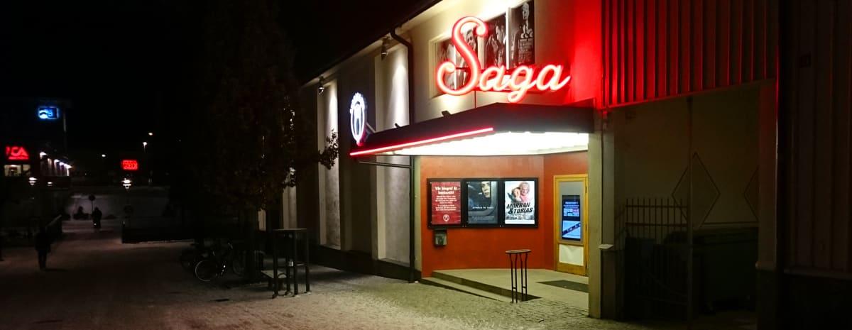 Entrén till Alingsås biograf Saga, med sin varmt välkomnande rödlysande neonskylt. Fotad en mörk höstkväll med ett tunt snötäcke på marken.