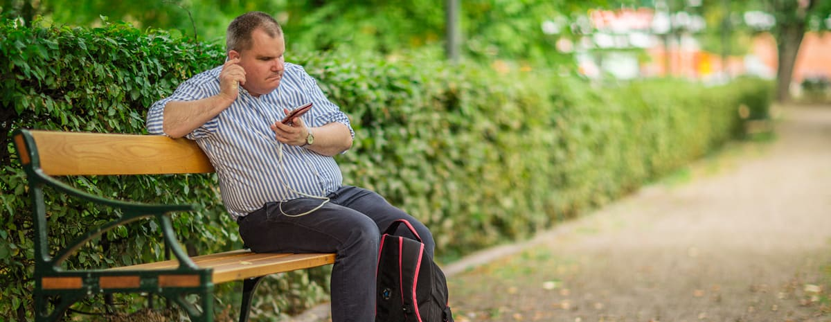 Fredrik sitter på en parkbänk, i handen har han sin mobil och en hörsnäcka i örat.