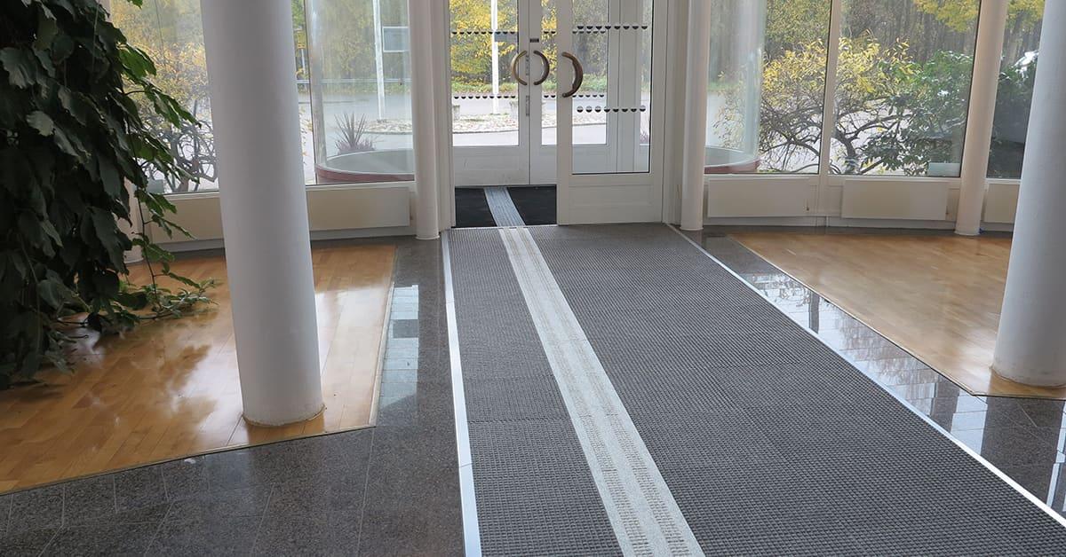 Vår entré på Matting i Alingsås. Längst bort i bild ser man en svart aluminiumprofilmatta i vindfånget. Innanför följer en lång grå Combi Tile. Bägge mattorna har ledstråk i avvikande färg.