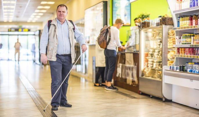 Fredrik följer ett ledstråk på Linköpings resecentrum, passerar Pressbyrån till höger.