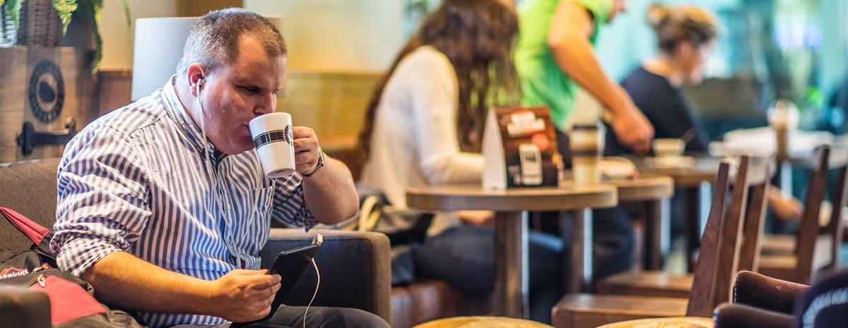Fredrik sitter i soffan på cafét och dricker kaffe. I handen håller han sin smartphone.