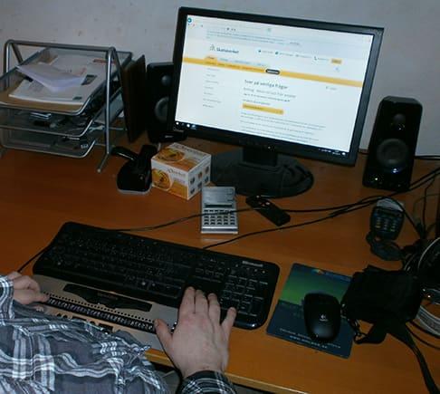 Fredrik söker på Skatteverkets hemsida. Bilden visar datorskärmen på skrivbordet och vid tangentbordet Fredriks specialtangentbord med punktskrift.