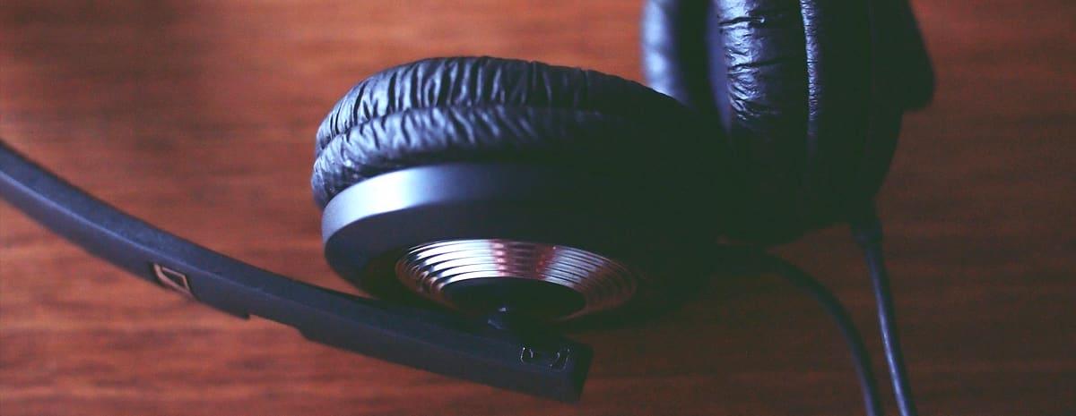 Närbild på svarta hörlurar på en träbrun bordsskiva.